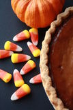 Candy Corn with black back ground and a pumpkin pie vertical Royalty Free Stock Photo