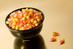 Candy Corn in Black Bowl. Halloween candy corn in black bowl on gold reflective surface Stock Photos
