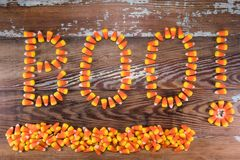 Candy Corn Boo! With Pile Below. Over wooden background royalty free stock photography