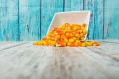 Candy corn. Being spilled onto wooden surface royalty free stock images
