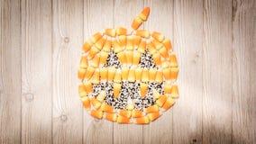 Candy corn forms a jack o` lantern pumpkin on wood royalty free stock image