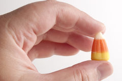 Candy corn. A hand holding a piece of candy corn Stock Photo
