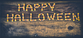 Candy Corn Happy Halloween 2. Happy Halloween spelled out in text using candy corn on a rustic harvest table. Nostalgia processed royalty free stock photography