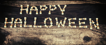 Candy Corn Happy Halloween 1. Happy Halloween spelled out in text using candy corn on a rustic harvest table. Rustic faded & grunge processed royalty free stock photos
