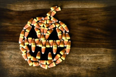 Candy Corn Jack-o-lantern with fangs. Fanged Halloween Jack-o-lantern made out of Candy Corn on top of a rustic harvest table. Rustic grunge processing stock images