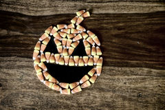 Candy Corn Jack-o-lantern. Halloween Jack-o-lantern made out of Candy Corn kernels on top of a rustic harvest table. Rustic faded, grunge processing stock photography