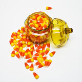 Candy Corn in Jar. Lots of candy corn in and around a pumpkin-shaped glass jar Royalty Free Stock Photos