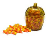 Candy Corn in Jar. Lots of candy corn in and around a pumpkin-shaped glass jar Stock Photos