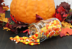 Candy corn in a mason jar spilling onto a table decorated for au Royalty Free Stock Image