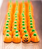 Candy Corn Pumpkins In A Row With Jack-o`-lantern Face. Several Candy Corn Pumpkins lined up on a cutting board.  One of the pumpkins has a Jack-o`-lantern face Royalty Free Stock Photography