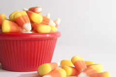Candy Corn in a Red Bowl. With candy corn spilled over Royalty Free Stock Photography