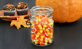 Candy corn in a rustic mason jar.  Pumpkin and cupcakes in the b Royalty Free Stock Images