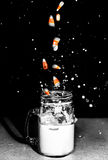 Candy Corn Splashing in Milk Glass. Candy Corn being dropped and Splashing in a Milk Mason Jar Glass Stock Images