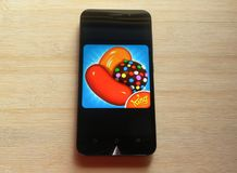 Candy Crush Saga app. Candy Crush Saga game app on smartphone kept on wooden table stock images