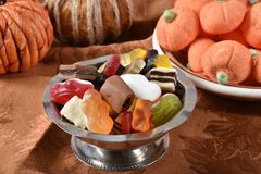 Halloween Candy. A candy dish of gelatin fruit candies, chocolates, and pumpkin marshmallows in the background for Halloween royalty free stock image