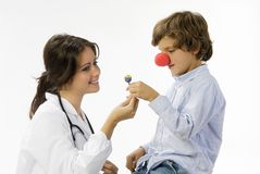 Candy and doctor. Young female doctor having a sweet approach with a little boy stock photo