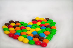 Candy drops in the form of heart. Heart lined with colorful candy pills royalty free stock photography