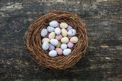 Candy easter eggs in birds nest. Happy Easter candy easter eggs in birds nest on dark vintage recycled wood background stock image