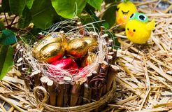 Candy eggs in wicker nest and toy chicken. Easter time Stock Image