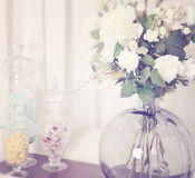 Candy and flower arrangement. Display of flowers in a glass vase and candy in glass jars stock photography