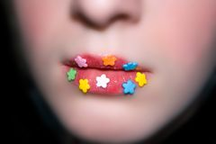 Candy flowers on lips, blured face. Blured woman face with candy flowers on lips. Isolated on black royalty free stock photo