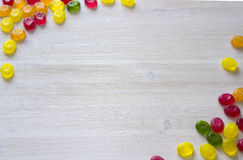 Candy frame background. Colorful candy decoration frame over wooden white background Stock Images