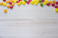 Candy frame background. Colorful candy decoration frame over wooden white background Stock Image