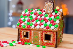 Candy ginger house background Christmas tree. Cute gingerbread man in front of his candy ginger house background the Christmas tree lights royalty free stock photography