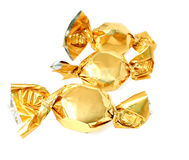 Candy in golden foil. Three candy in golden foil isolated on white stock images