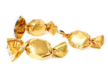 Candy in golden foil. Three candy in golden foil isolated on white royalty free stock images