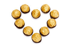 Candy in golden foil in the shape of a heart Stock Images