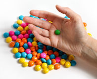 Candy with hand. Colored candy with womans hand holding one green candy Stock Images