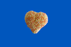 Candy Heart. Encrusted with yellow and orange colored sugar, balls isolated on yellow background Stock Photos