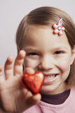 Candy heart. Young girl presenting red candy heart royalty free stock image