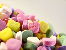Candy Hearts. Conversation hearts piled up with the words it's love visible Royalty Free Stock Image