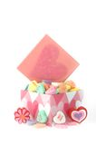 Candy and hearts. Decorative cardboard box is full of candy hearts. Box lid is propped at back of box and has a glittery pink heart on it. Daisy sits at left stock photography