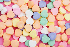 Candy Hearts. Multi color candy hearts on a pink background stock photo