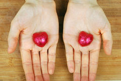 Candy hearts in the background in female hands. Two candy hearts in the background in female hands Royalty Free Stock Photography