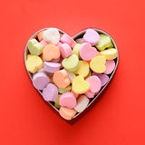 Candy Hearts in Box. High angle view of a bunch of pastel candy hearts in a heart shaped box for Valentines Day. Square format on a red background, the candies stock images