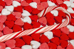 Candy hearts,cane,Valentines,day. A candy cane laying in a assortment of candy hearts royalty free stock photography