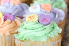 Candy Hearts on Cupcakes. Romantic candy hearts on pastel-colored cupcakes - True Love and Be Mine in focus royalty free stock image