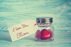 Candy hearts in a glass jar with tag. On wooden background stock photos