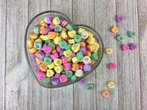 Candy hearts in a heart shaped bowl. Colorful candy hearts in a heart shaped glass bowl on a wood surface royalty free stock image