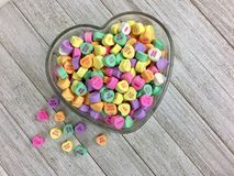 Candy hearts in a heart shaped bowl. Colorful candy hearts in a heart shaped glass bowl on a wood surface royalty free stock photo