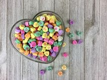 Candy hearts in a heart shaped bowl. Colorful candy hearts in a heart shaped glass bowl on a wood surface royalty free stock photos