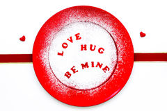 Candy hearts message on red plate with confectionery sugar Royalty Free Stock Image