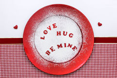 Candy hearts message on red plate with confectionery sugar Royalty Free Stock Photography