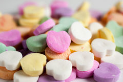 Candy Hearts. Pastel colored candy hearts in a pile on a white surface royalty free stock photography