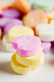 Candy Hearts. Pastel colored candy hearts in a pile on a white surface royalty free stock photo
