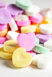 Candy Hearts. Pastel colored candy hearts in a pile on a white surface stock photo
